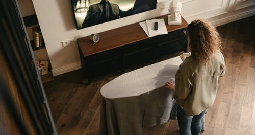 A Woman Flat Ironing A Table Cloth While Watching A Television