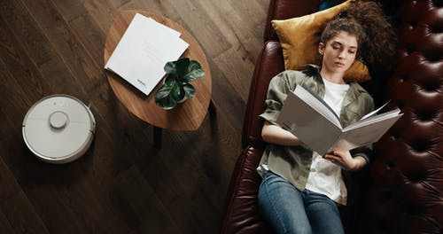 A Woman Lies On A Couch Reading A Book While A Robovac Cleans The Floor