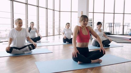 Women Practicing Yoga Inside the Yoga Studio