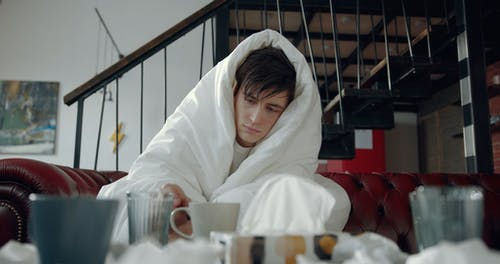 A Sick Man Cover Himself With A Thick Blanket While Drinking Hot Tea