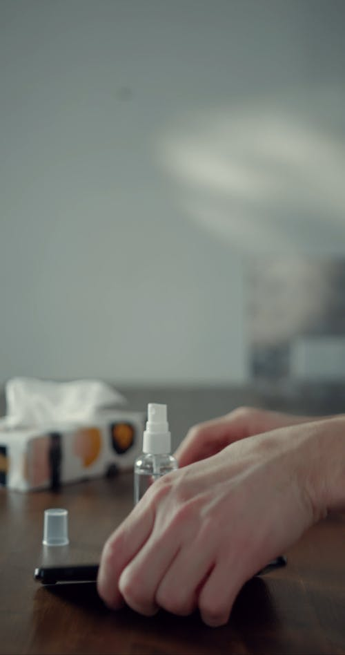 A Man Using A Sanitizer To Clean His Phone