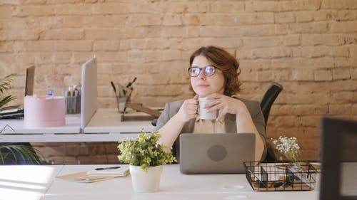A Working Woman Day Dreaming While Having A Coffee Break