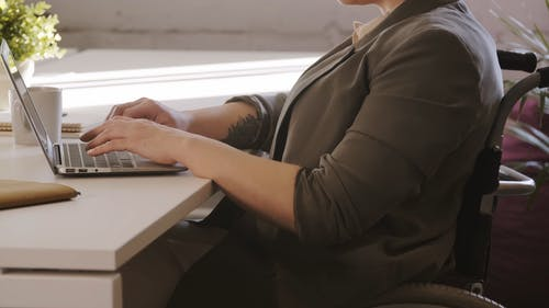 A Person On Wheelchair Busy Typing On A Laptop