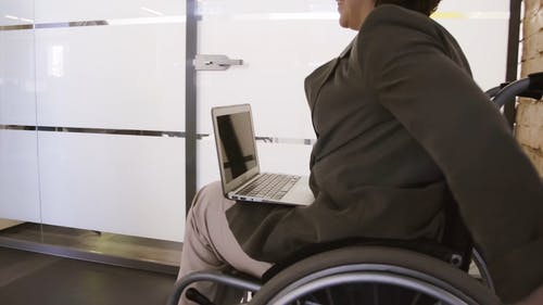 A Woman In Wheelchair Pushes Herself With A Laptop On Her Lap