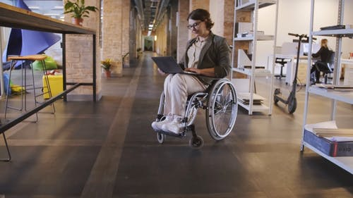 A Woman In A Wheelchair Working With A Laptop In The Office