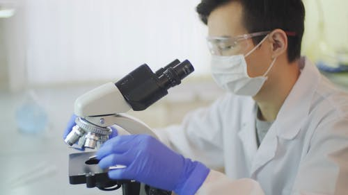 A Male Scientist Studying Specimen With A Microscope