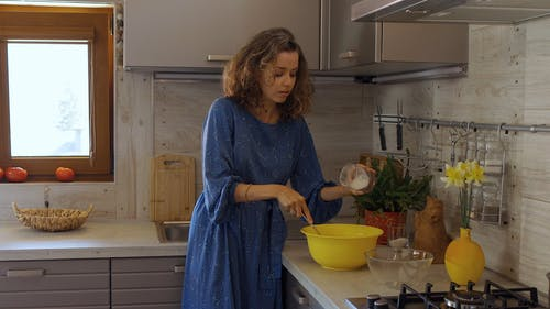 Woman Adding Flour to a Mixing Bowl