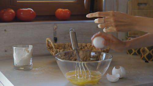 Woman Breaking Eggs In Preparation For Cooking