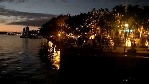 Silhouette of People Walking by the Riverside
