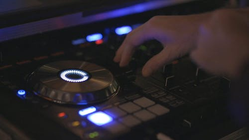 A Disc Jockey Mixing Music With His Equipment