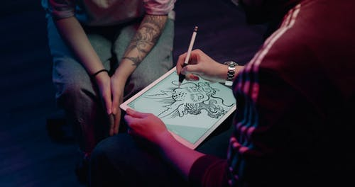 A Tattoo Artist Using An Ipad In Discussing To A Customer A Tattoo Design