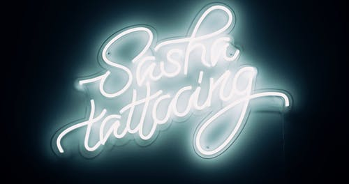 A Lighted Signage Of A Tattoo Shop