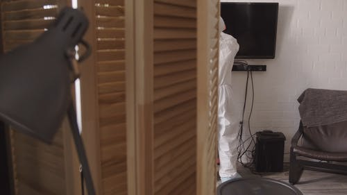 Person Wearing Protective Coverall While Disinfecting Inside A House