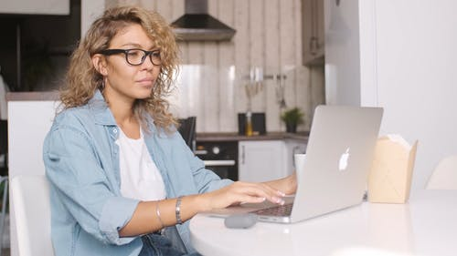 Woman Drinking Her Coffee While Using Her Laptop