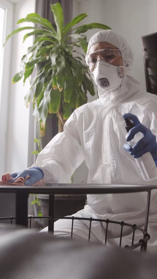 A Woman In Full Protective Gear Disinfecting A Table