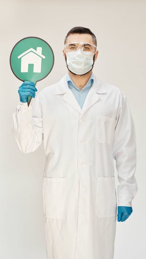 A Doctor Holding A Sign Meaning To Stay Home For Safety