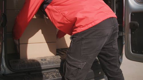 A Man Unloading Boxes From A Van
