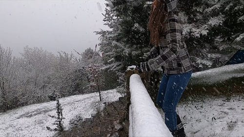 Woman in Winter Jacket Leaning on a Railing While Snowing