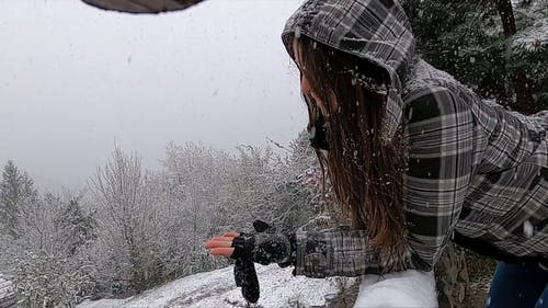 Woman in Winter Jacket Leaning ona Railing While Snowing