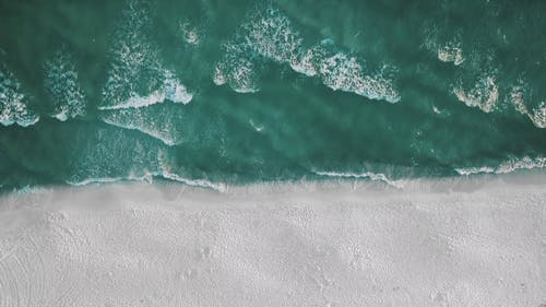 Top View of Beach Waves Crashing on Seashore