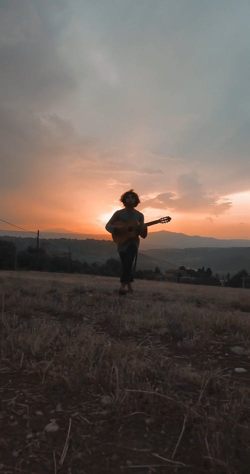Man Playing His Guitar While Walking In A Hill