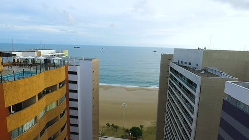 Drone Flying Over The Beach In Front Of Hotels And Resorts