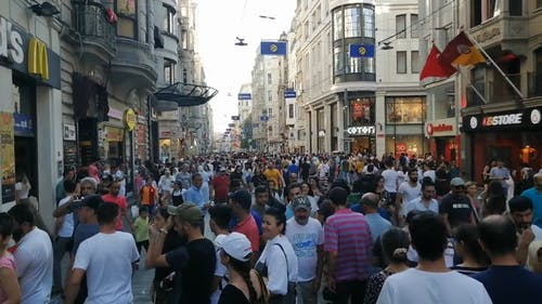 A Crowd Of People Packing A Busy Street