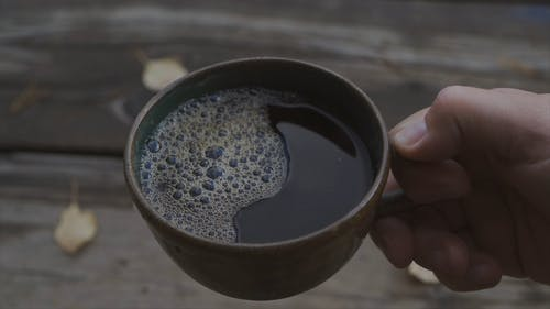 Person Holding A Cup Of Black Coffee