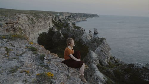 A Woman Sitting on the Edge of a Cliff Enjoying the Ocean View