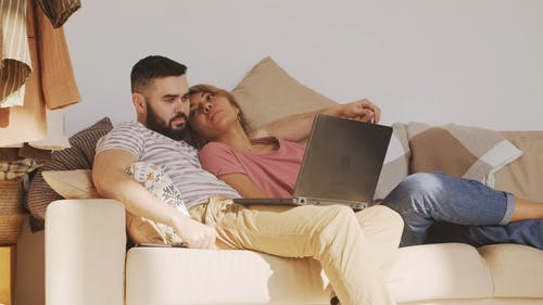 Man And Woman Lounging On A Sofa
