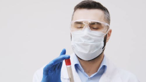A Man Holding A Test Tube With Blood To Be Examine