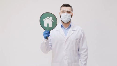A Man Wearing Protective Gear Holding A Stay At Home Sign
