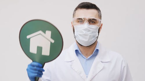 A Health Worker Holding A Stay At Home Signboard