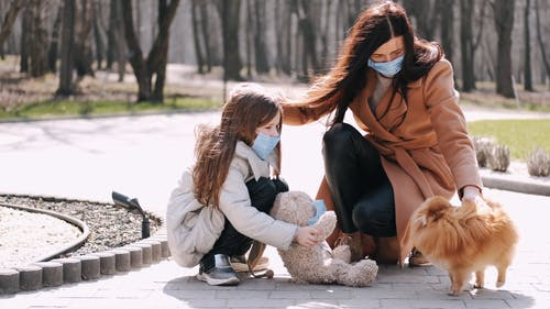 Mother and Daughter with Face Masks at the Park With Dog
