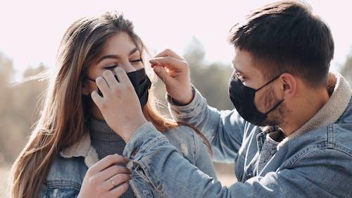 Man Adjusting Woman's Face Mask