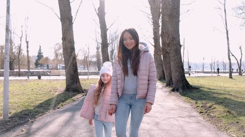A Mother And Daughter Walking In The Park