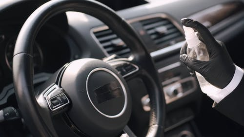 Person With Latex Gloves Spraying Disinfectant on Steering Wheel