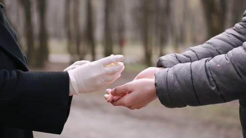 Person With Latex Gloves Sharing Hand Sanitizer