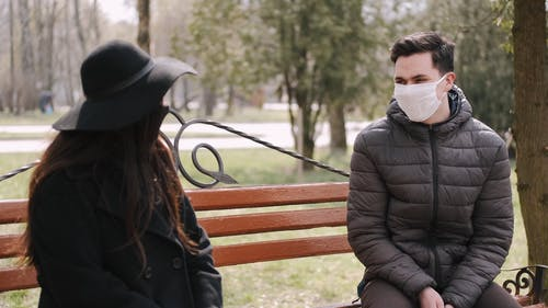 Couple With Face Masks Sitting on a Bench and Talking