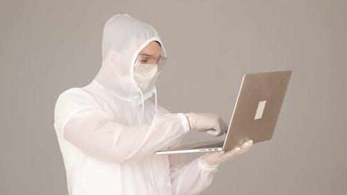 Man in a Hazmat Suit Typing on a Laptop
