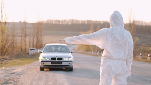 Person In a Hazmat Suit Signaling a Car to Stop