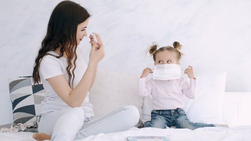 A Mother Teaching Her Kid How To Wear A Face Mask