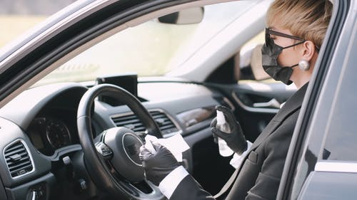 Woman With Face Mask Spraying Disinfectant on Steering Wheel