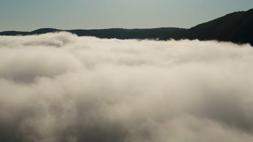 Drone Shot Of Low Lying Clouds Over The Mountain Valley