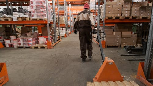 A Male Worker Using A Pallet Truck Inside The Warehouse