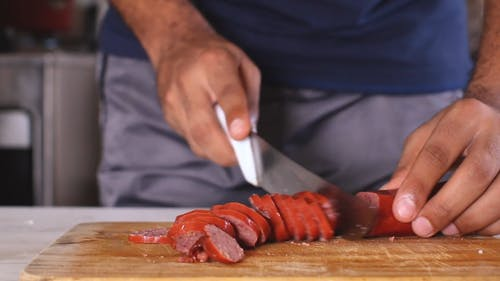 Man Slicing A Sausage Into Pieces With A Knife