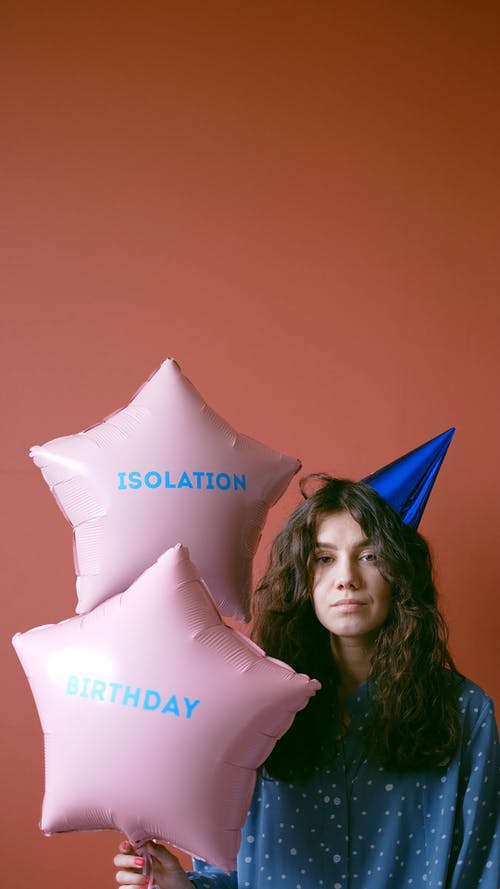 Woman With a Party Hat Holding a Balloon