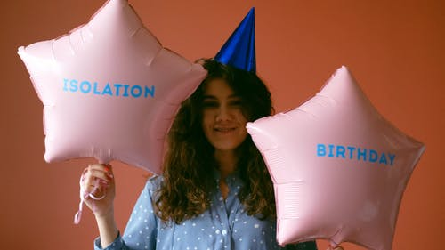 Woman With a Party Hat Holding Balloons
