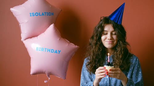 Woman With a Party Hat Holding a Cupcake and Blowing a Candle