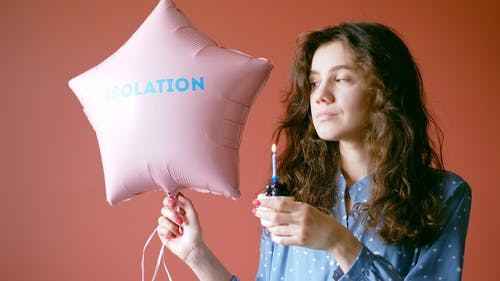 Woman Holding a Balloon and Blowing a Candle